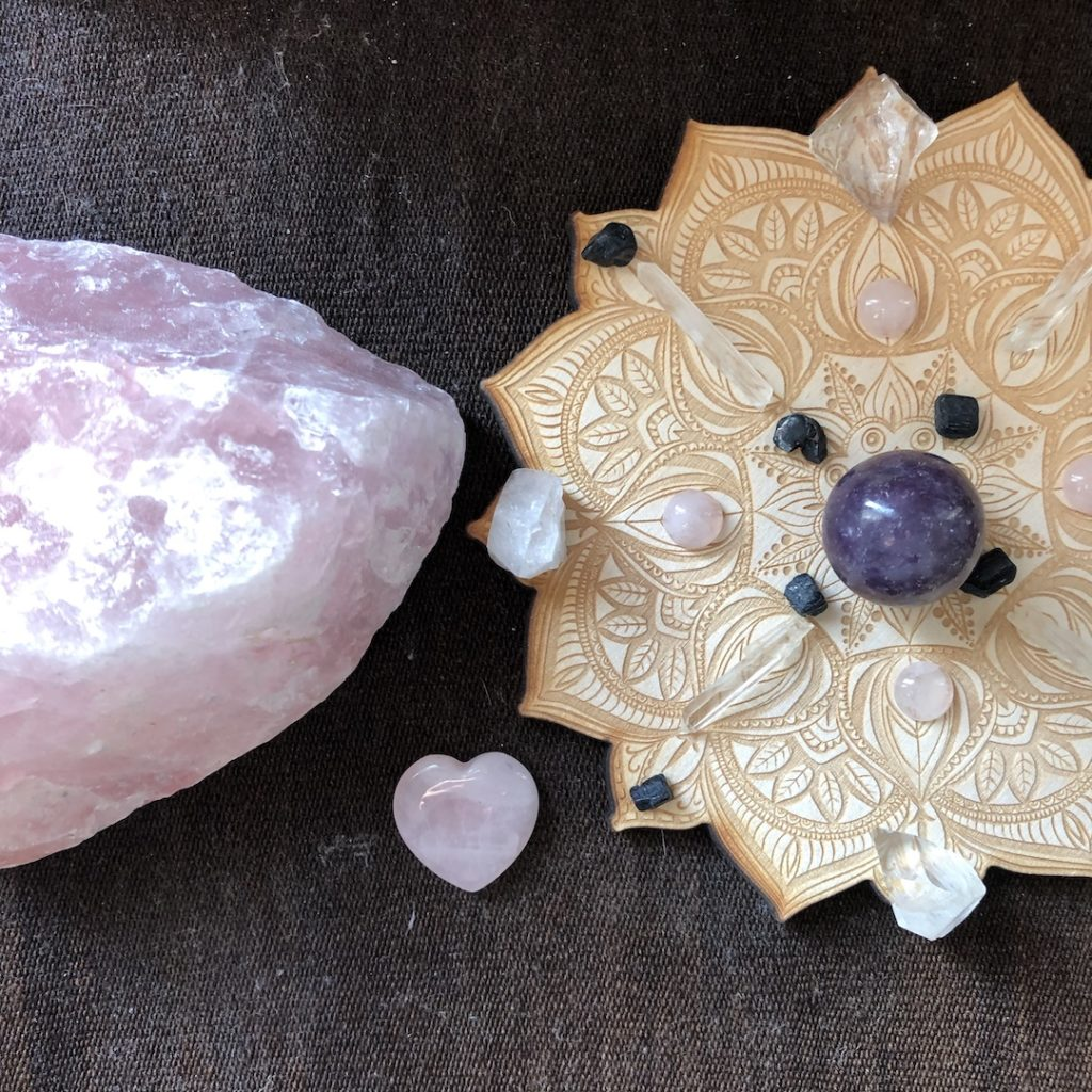 rose quartz crystal and crystals on a wooden mandala - ways to be present